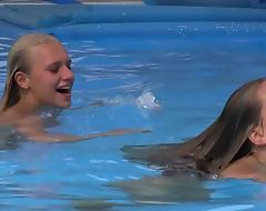 Two beautiful girls swimming together with licking by slay rub elbows with pool